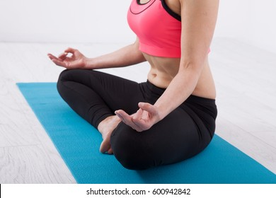 Sport. Fitness Yoga woman. Woman doing yoga indoors. Woman sitting in lotus pose with crossed legs in fitness room