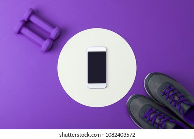 Sport flat lay composition with purple dumbbells, gray shoes, white round paper circle and blank mobile phone mockup on lilac paper background.
