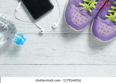 Sport flat lay purple shoes, smartphone and workout equipments on white wooden background with copyspace for your text. Concept healthy lifestyle and diet.