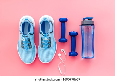 Sport flat-lay with sneakers and water on pink table top view
