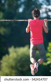 Sport girl athlete is Chin-ups and Pullups training on an abandoned sports field. Pull-up on the bar. Athlete Outdoors.