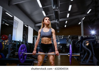 Sport girl with a barbell in her arms in the gym