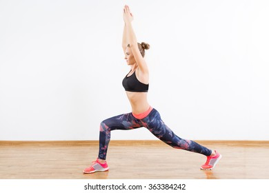 Sport girl with dark hair wearing pink snickers, dark leggings and black short top doing crescent moon at gym, fitness, white wall and wooden floor.
