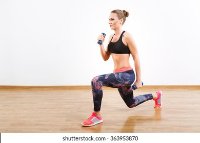 Sport girl with dark hair wearing pink snickers, dark leggings and black short top doing lunge with dumbbells at gym, fitness, white wall and wooden floor.