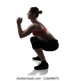 sport girl doing squatting exercise, silhouette studio shot over white background