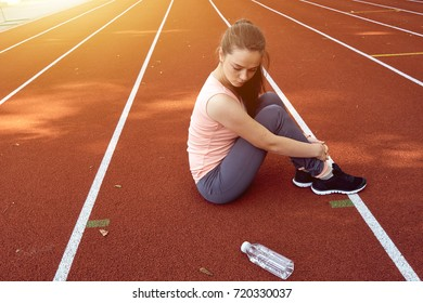 Sport girl having rest and seating on a running track