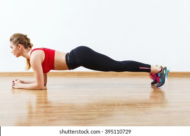 Sport girl with light brown hair wearing snickers, dark leggings and red short top doing plank at gym, fitness, white wall and wooden floor.