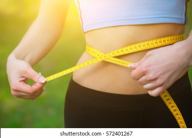 Sport girl measuring waist with yellow measuring tape, reducing excess weight. Healthy lifestyle.