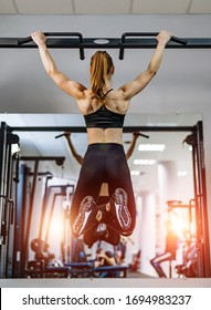 The sport girl pulls up on the horizontal bar in the gym. Art photo. Doing twisting on bar. Back photo
