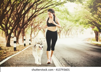 sport girl is running with a dog (siberian husky) at the morning on the road