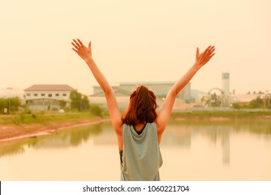 Sport girl show hand up for exercise and diet successes over pond at the park background. Concepts of relaxing , fresh air in the morning , park and outdoor activity , exercise for healthy. warm tone.