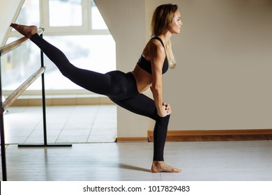 sport girl smiling and looking in mirror while stretching body in fitness class