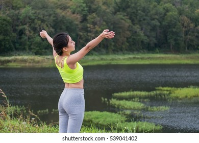 Sport girl standing with raised arms and enjoying a beautiful nature.