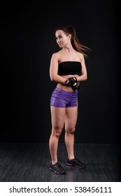 Sport girl stands and looks aside on black background.