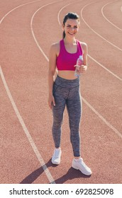 Sport girl workout. Young  girl hold bottle of water at stadium do some training and looking at camera. Exercise. Fitness. Health.