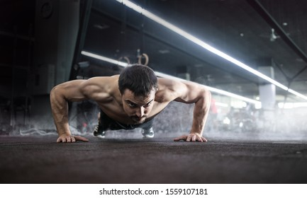 Sport. Handsome man doing push ups exercise with one hand in fitness gym.