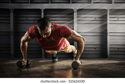 Sport. Handsome man doing push ups exercise with one hand in fitness gym