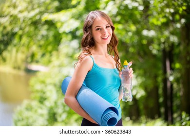 Sport happy woman with yoga mat outdoors.