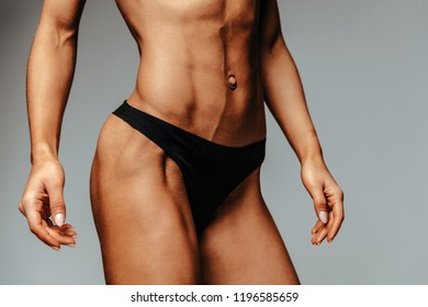 Sport. Health. Body. Cropped image of sportswoman in black bikini, showing her hip muscles and abs, on grey background