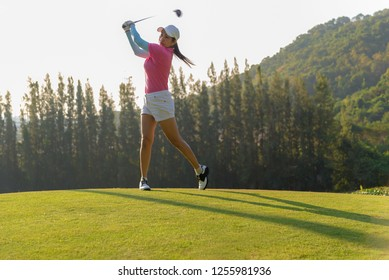 Sport Healthy. Asian sporty woman golf player doing golf swing tee off on the green evening time, she presumably does exercise outdoors.  Healthy and Lifestyle Concept.