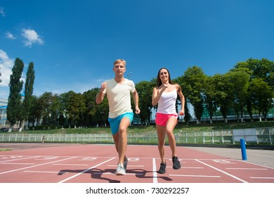 Sport and healthy fitness. Couple running on arena track. Man and woman sunny outdoor on blue sky. Coach and trainer at workout. Runner on competition and future success.