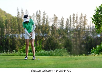 Sport Healthy. Golfer asian sporty woman focus putting golf ball on the green golf on vacation day.  Healthy and Lifestyle Concept