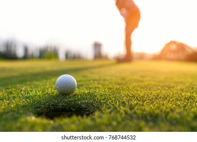 Sport Healthy. Golfer asian sporty woman focus putting golf ball on outdoor the green golf on sun set evening time.. Healthy and Lifestyle Concept