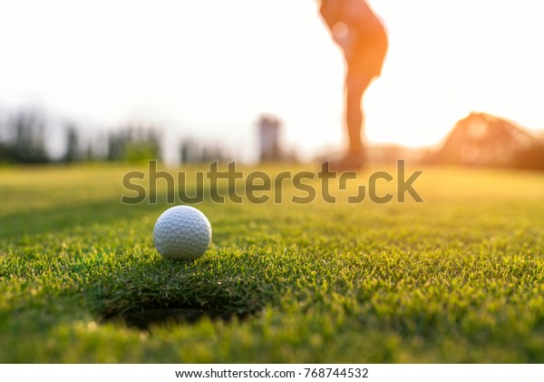 Sport Healthy. Golfer asian sporty woman focus putting golf ball aim on outdoor the green golf on sunset evening relax time.  Healthy and Lifestyle Concept