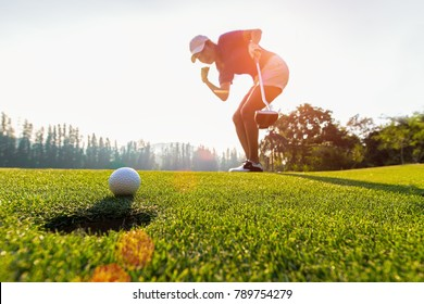 Sport Healthy. Golfing game. Asian woman golfer action to win after long putting golf ball on the green golf, outdoors sunset time, copy space.  Healthy Concept