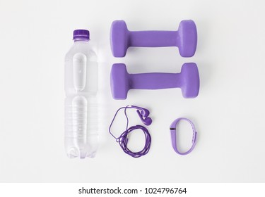 sport and healthy lifestyle concept - close up of dumbbells, fitness bracelet, earphones and water bottle in trendy ultra violet color on white background