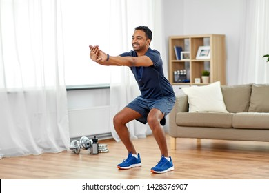 sport and healthy lifestyle concept - smiling indian man with fitness tracker exercising and doing squats at home