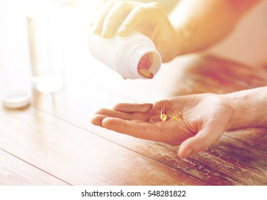 sport, healthy lifestyle, medicine, nutritional supplements and people concept - close up of man in fitness bracelet with glass of water pouring fish oil capsules from jar to hand