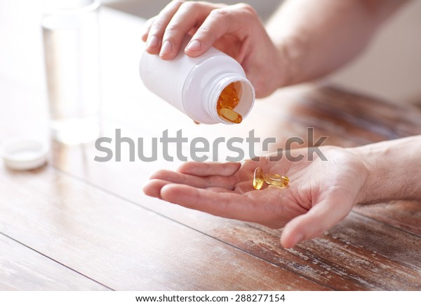sport, healthy lifestyle, medicine, nutritional supplements and people concept - close up of man with glass of water pouring fish oil capsules from jar to hand