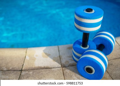 Sport and healthy lifestyle. Pair of plastic dumbbells for aqua fitness  near swimming pool on summer day outdoors, nobody