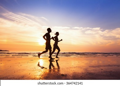 sport and healthy lifestyle, two people jogging at sunset on the beach