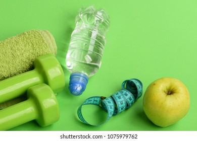 Sport and healthy regime equipment. Healthy lifestyle and low calorie food concept. Barbells near green apple. Dumbbells in green color, water bottle, measure tape, towel and fruit on green background