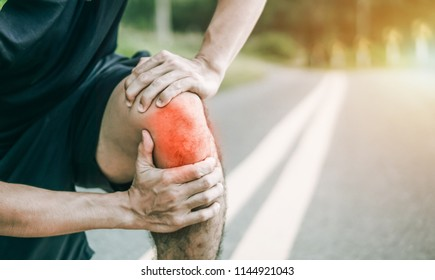 Sport injury. Accident concept,Young fitness man holding his sports leg injury, after running and exercise outside in summer.