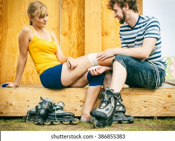 Sport injury. Couple of skaters outdoor. Young woman suffering from leg pain after taking a fall on the asphalt, man is helping bandaging her injured knee
