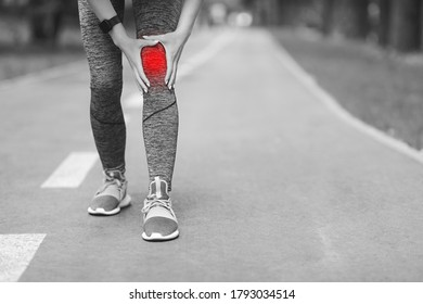 Sport Injury. Unrecognizable Woman Massaging Inflamed Knee Zone With Red Sore Spot, Suffering From Leg Trauma After Training Outdoors, BW Style