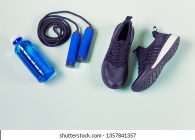 Sport items - jumping rope, sport shoes, blue bottle with water. Items arranged on light green background. Photo with copy blank space.