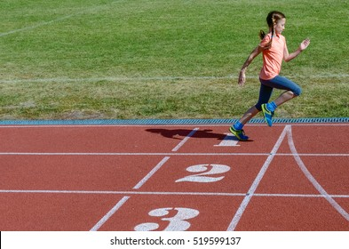 Sport for kids, active child running on stadium track, little girl training, fitness concept