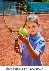 Sport kids girl with racket and ball on  brown tennis court.
