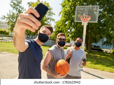 sport, leisure games and male friendship concept - group of happy men or friends wearing face protective masks for protection from virus disease taking selfie on outdoor basketball playground