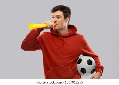 sport, leisure games and people - happy man or football fan in red hoodie with soccer ball blowing vuvuzela horn over grey background