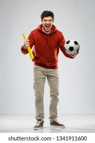 sport, leisure games and people - happy man or football fan in red hoodie with soccer ball and vuvuzela over grey background