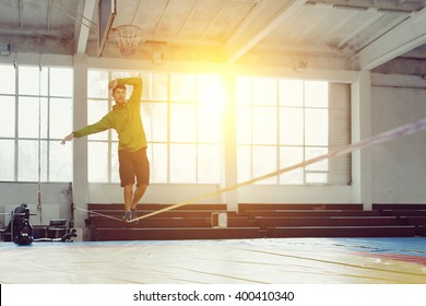 Sport, leisure, recreation and healthy active lifestyle concept - man slacklining walking and balancing on a rope, slackline in a sports hall