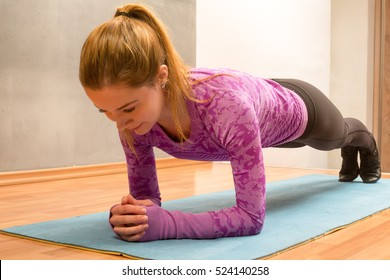 Sport and lifestyle concept. Slim fitness young girl with ponytail doing planking exercise indoors at home gymnastics.