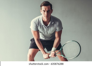 Sport, lifestyle and  people concept - young man tennis player in action on gray background.