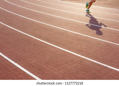 Sport. Male legs in colorful sneakers on running track stadium. Close-up on sports shoes of a running man. Concept run