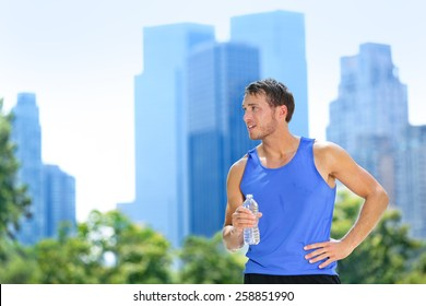 Sport man drinking water bottle in New York City. Male runner sweaty and thirsty after run in Central Park, NYC, Manhattan, with urban buildings skyline in the background.